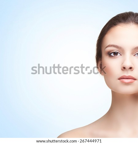 Half-face Portrait of Beautiful Young Woman on the Blue Background. Head and Shoulders - stock photo