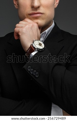 Half face portrait of successful business man in a black suit on grey background. - stock photo
