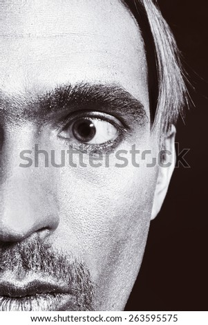 Half face portrait of young man with silver paint on his face - stock photo