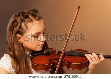 Half-face view of beautiful girl playing violin - stock photo