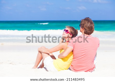 half face view of happy young couple sitting at tropical Mexico beach