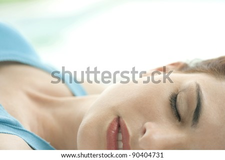 Half face view of young woman sleeping at home during the day.