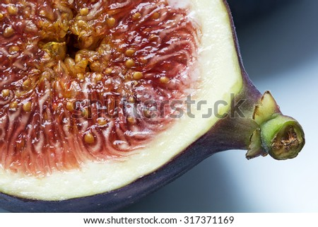 half fig, macro shot shows the juicy red fruit pulp with the seeds - stock photo