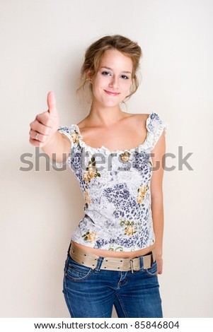 Half figure portrait of a cheerful fashionable young blond woman showing thumbs up. - stock photo