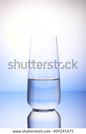 Half-filled drinking glass with reflection in drops of water on white and blue background - stock photo
