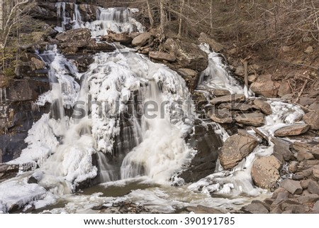 Half frozen Bastion Falls beside Route 23A on Lake Creek, about 1/2 miles downstream of Kaaterskill Falls in the Catskills Mountains of New York. - stock photo