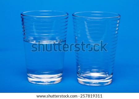 Half full, half empty glass of water. - stock photo