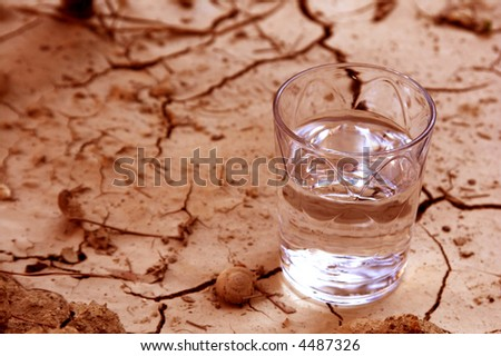 half full water over cracked earth - stock photo