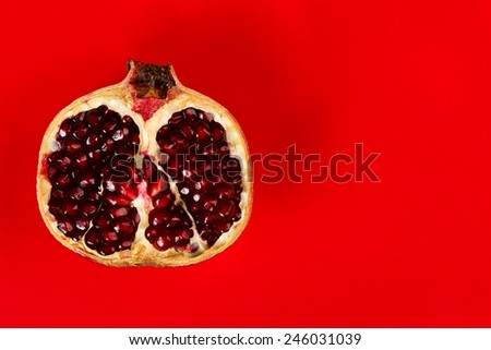 Half grenadine on the left side over red background - stock photo