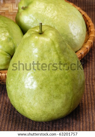 Half guava and slices with the complete one on table - stock photo