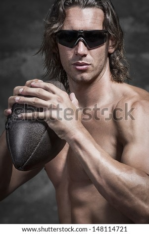 half lenght of bare chested muscle man is wearing sunglasses and holding american football ball in his hands - stock photo