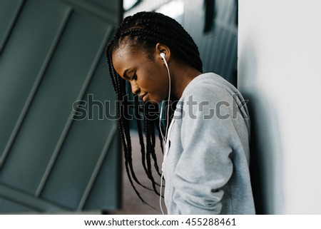Half-length close-up portrait of excited young African girl wearing hoodie and cool earphones standing looking down