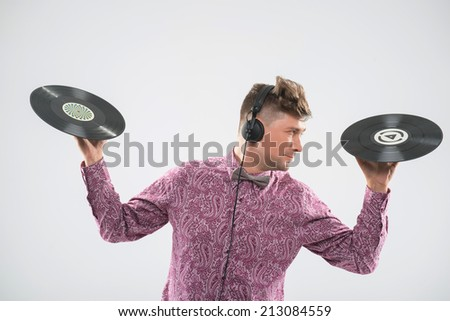 Half-length closeup portrait of excited young DJ with stylish haircut, bow tie and headphones posing with two vinyl records looking sideways isolated on white background - stock photo