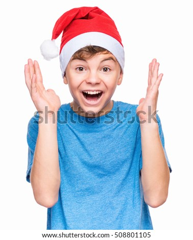 Half-length emotional portrait of caucasian teen boy wearing Santa Claus hat, surprised. Teenager in blue t-shirt looking at camera. Holiday Christmas concept - happy cute child isolated on white