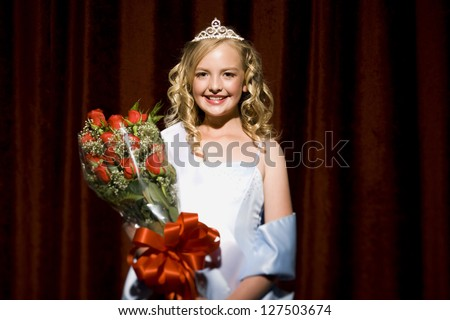 Half length of a beauty pageant winner smiling and holding roses
