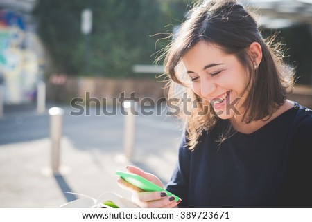 half length of a young beautiful brown hair caucasian woman in town reading book while using a smartphone looking downward, smiling - culture, technology, social network concept - stock photo