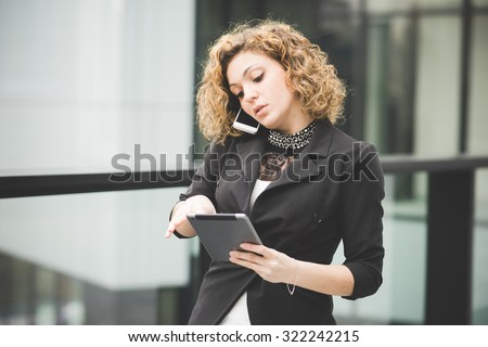 Half length of a young beautiful caucasian contemporary businesswoman talking smartphone while using a tablet looking down the screen- technology, network, business, finance concepts - stock photo