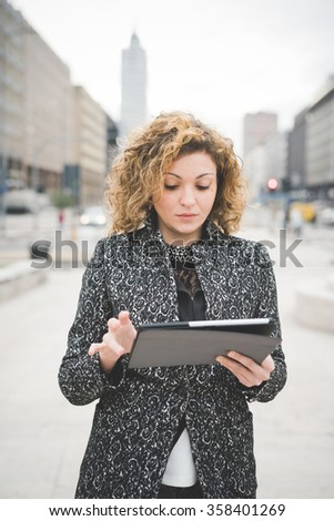 Half length of a young beautiful caucasian contemporary businesswoman walking through the streets of the city using a tablet looking down the screen - technology, network, business, finance concepts - stock photo
