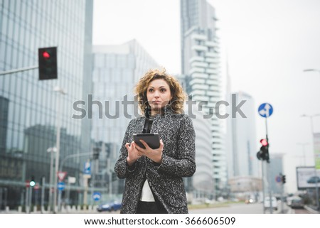 Half length of a young beautiful caucasian contemporary businesswoman walking through the streets of the city using a tablet overlooking - technology, network, business, finance concepts - stock photo