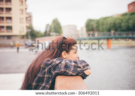 Half length of a young beautiful reddish brown hair caucasian girl leaning against a windowsill overlooking - pensive, youth, freshness concept - dressed with checked shirt - stock photo