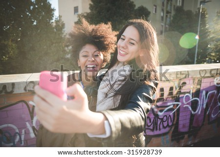 Half length of two multiethnic beautiful young woman black and caucasian having fun in town, hugging and laughing, taking a selfie - carefreeness, freshness, youth concept - stock photo