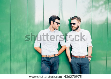 Half length of two young blonde and black hair modern businessman posing leaning against a wall, talking one to each other - business, successful concept