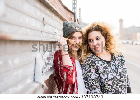 Half length of two young curly and straight blonde hair caucasian woman leaning on a wall, one playing with the other's hair, use it in shape of mustache - youthful, carefreeness, friendship concept - stock photo