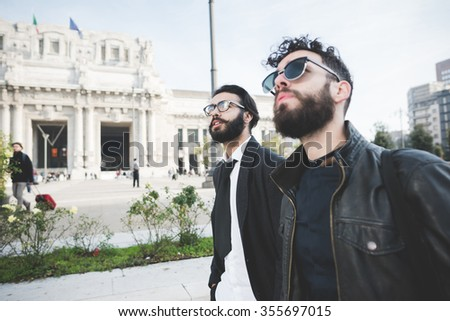 Half length of two young handsome caucasian bearded brown hair businessmen walking in the street of the city, both looking upward right - business, work concept - stock photo