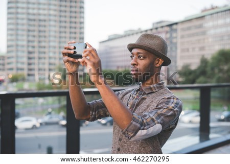 Half length of young beautiful afro black man outdoor in the city holding a smart phone taking picture - technology, social network, travel concept