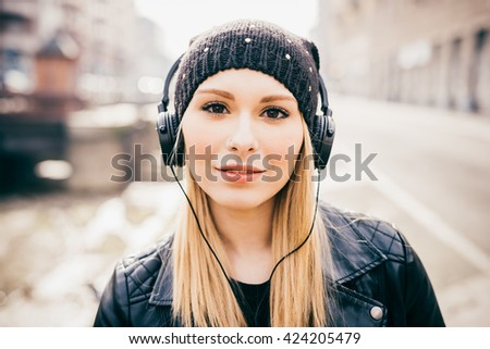 Half length of young beautiful blonde straight hair woman in the city with headphones listening to music, looking in camera smiling - happiness, relaxing, technology concept - stock photo