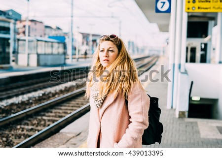 Half length of young beautiful caucasian blonde woman at the train station waiting for train overlooking pensive - commuter, transport, serious concept - stock photo
