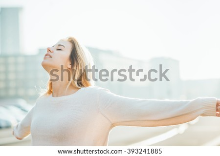 Half length of young beautiful caucasian woman feeling free with arms wide open in the city back light - liberty, freedom, girl power concept - stock photo