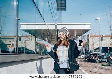 Half length of young beautiful caucasian woman listening music with headphones outdoor in city backlight, dancing and smiling - music, relaxing, technology concept