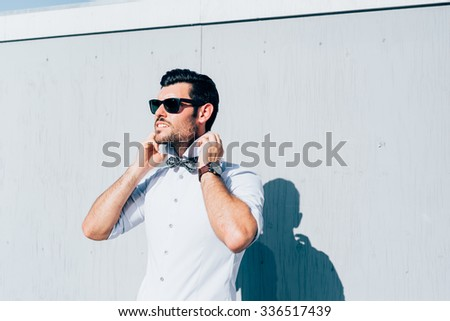 Half length of young handsome black hair caucasian modern businessman posing leaning against a wall, overlooking right, wearing bow tie - business, successful concept - stock photo
