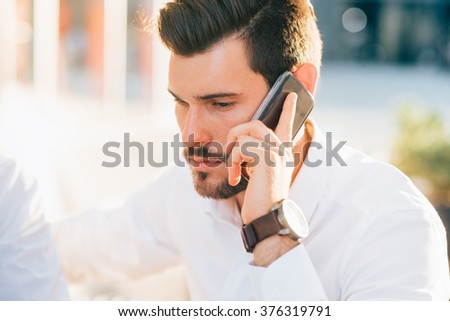 Half length of young handsome black hair caucasian modern businessman talking smartphone in city backlight- business, working, communication concept - stock photo