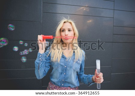 Half length of young handsome blonde caucasian girl having fun playing with soap bubble in the city wearing jeans shirt and floral skirt - emancipation, carefree, youth concept - stock photo