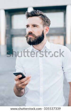 Half length of young handsome blonde caucasian modern businessman holding a smartphone, overlooking right, pensive - business, working, technology concept - stock photo