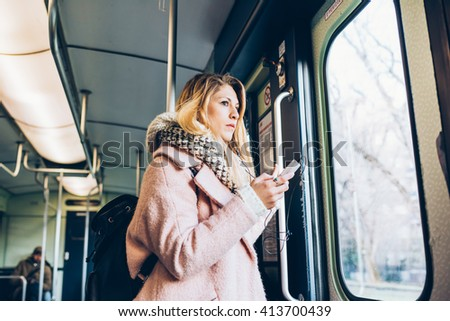 Half length of young handsome blonde straight hair woman traveling in the underground, holding a smart phone, looking outside the window - technology, commuting, transport concept