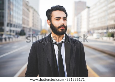 Half length of young handsome caucasian bearded businessman posing outdoor in the street, overlooking pensive - business, thoughtful, serious concept