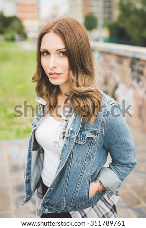 Half length of young handsome caucasian blonde straight hair woman looking in camera, serious, wearing white shirt and jeans jacket - thinking future, pensive concept - stock photo