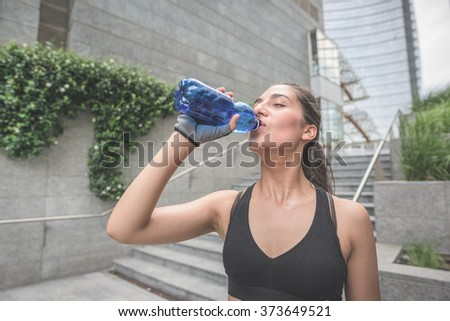 Half length of young handsome caucasian brown hair sportive woman drinking water from a bottle, having a break from training - relaxing, break, training concept - stock photo