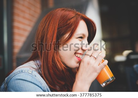 Half length of young handsome caucasian reddish hair woman drinking a glass of juice  overlooking smiling - relaxing, break, happiness concept - stock photo