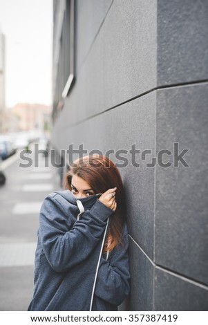 Half length of young handsome caucasian reddish straight hair woman posing leaning against a wall, trying to hide her face using sweatshirt - stock photo