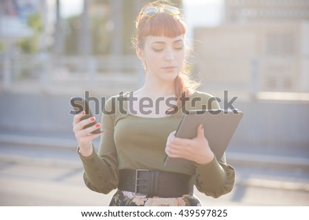 Half length of young handsome caucasian redhead woman using a smartphone, looking downward and tapping the screen while holding a tablet on the other hand - multitasking, working, technology concept - stock photo