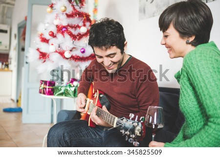 Half length of young handsome man and woman couple sitting on the sofa, he is playing guitar, she is looking at him, laughing - music, christmas, relax concept - stock photo