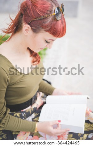 Half length of young handsome reddish pin up italian girl looking downward reading a book - culture, relax, break concept - stock photo