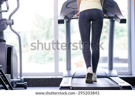 Half length photo of a fit young woman standing back to us on a treadmill, wearing grey leggings and white sneakers in a fitness club - stock photo