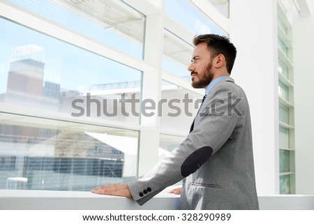 Half length portrait of a confident businessman conceived looks in office window while rest after conference, young successful male financier dressed in suit thinking about something during work break  - stock photo