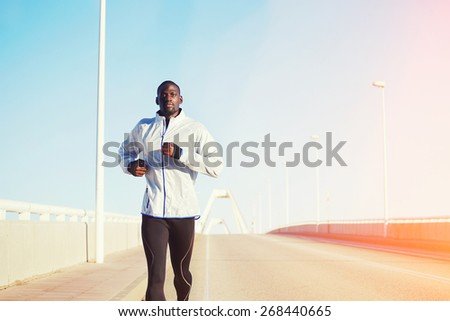 Half length portrait of a fit and athletic man running on a bridge road promenade outside - copy space area, dark skinned runner jogging against bright sky background, flare light with cross process - stock photo