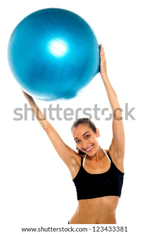 Half length portrait of a fit woman holding big blue swiss ball above her head. Fitness concept